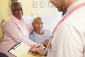 Close Up Of Doctor Updating Patient Notes — Stock Photo