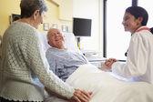 Female Doctor Talking To Senior Couple In Hospital Room — Stock Photo