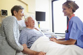 Nurse Talking To Senior Couple In Hospital Room — Stock Photo