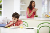 Son Does Homework As Mother uses Laptop In Background — Stock Photo