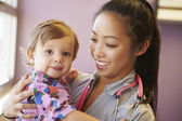 Young Girl Being Held By Female Pediatric Doctor — Stock Photo