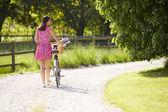 Rear View As Woman Pushes Bike Along Country Lane — Foto Stock