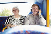 Man Disturbing Passengers On Bus Journey With Loud Music — Stock Photo