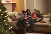 Family Celebrating Christmas At Home Viewed From Outside — Foto de Stock