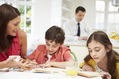 Mum Helps Children With Homework As Dad Works In Background — Stock Photo