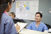 Male And Female Nurse In Discussion At Nurses Station — Stock Photo