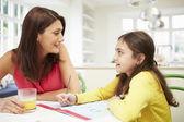Mamma att hjälpa dottern med läxor — Stockfoto