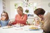 Family With Young Baby Eating Meal At Home — Stock Photo