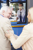 Woman Helping Senior Man To Board Bus — Stock fotografie