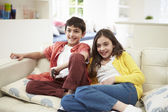 Two Hispanic Children Sitting On Sofa Watching TV Together — Stock Photo