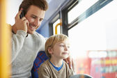 Father Using Mobile Phone On Bus Journey With Son — Stockfoto