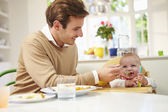 Father Feeding Baby Sitting In High Chair At Mealtime — Zdjęcie stockowe
