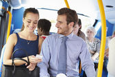 Businessman And Woman Looking At Mobile Phone On Bus — Foto de Stock