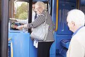 Senior Couple Boarding Bus And Using Pass — Stock Photo