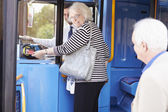 Senior Couple Boarding Bus And Using Pass — Stock Photo