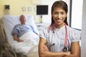 Portrait Of Female Doctor With Patient In Background — Stock Photo