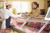 Butcher Serving Customer In Shop — Stock Photo