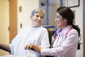 Äldre skjuts kvinnlig patient i rullstol av läkare — Stockfoto