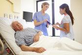 Medical Team Meeting As Senior Man Sleeps In Hospital Room — Stock Photo