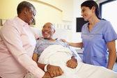 Nurse Talking To Senior Couple In Hospital Room — Stock Photo