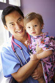 Young Girl Being Held By Male Pediatric Nurse — Stock Photo