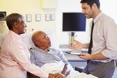 доктор говорить пожилые супружеские пары на уорд — Стоковое фото