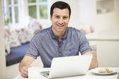Hispanic Man Using Laptop In Kitchen At Home — Foto de Stock