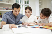 Father Helping Children With Homework Using Digital Tablet — Stock Photo