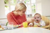 Mother Feeding Baby Sitting In High Chair At Mealtime — Stock Photo