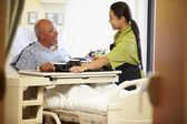 Senior Male Patient Being Served Meal In Hospital Bed — Stock Photo