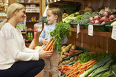 Mother And Daughter Choosing Fresh Vegetables In Farm Shop — Stock Photo