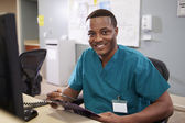 Portrait Of Male Nurse Working At Nurses Station — Stock Photo