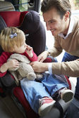 Father Putting Young Girl Into Car Seat — Stock Photo