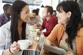 Two Female Friends Meeting In Busy Coffee Shop — Foto de Stock