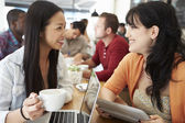 Two Female Friends Meeting In Busy Coffee Shop — Stok fotoğraf