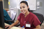 Portrait Of Female Nurse Working At Nurses Station — Stock Photo