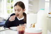 Schoolgirl With Digital Tablet And Mobile Eating Toast — Stock Photo