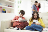 Children Playing With Digital Devices As Parents Make Meal — Стоковое фото