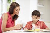 Mamma att hjälpa sonen med läxor — Stockfoto