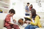 Children Playing With Dog On Sofa As Parents Make Meal — Stock Photo