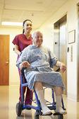 Starszy mężczyzna pacjenta jest wciśnięty na wózku inwalidzkim przez pielęgniarki — Zdjęcie stockowe