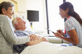 Female Doctor Talking To Senior Couple In Hospital Room — Stock Photo
