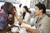 Two Male Friends Meeting In Busy Coffee Shop — Stock Photo