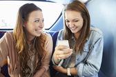 Zwei junge frauen, die lesen-text-nachricht auf bus — Stockfoto