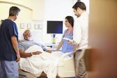 Medical Team Meeting With Senior Man In Hospital Room — Stock Photo