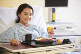 Female Patient Enjoying Meal In Hospital Bed — Stock Photo