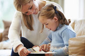 Mother And Daughter Reading Story At Home Together — Stock Photo