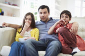 Father And Children Sitting On Sofa Watching TV Together — Stock Photo