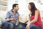 Hispanic Couple Sitting On Sofa Arguing — Stockfoto