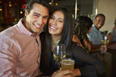 Couple Enjoying Drink At Bar With Friends — Stock Photo